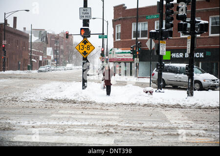 Chicago, Il, USA. 5th Jan, 2013. A woman waits to cross Elston Avenue in Chicago as heavy snowfall and rapidly dropping - Stock Photo