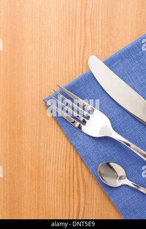 silver fork and knife as utensils on napkin at wooden background - Stock Photo