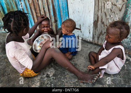 A girl feeds his younger brother by rice in the slum of Cité Soleil, Port-au-Prince, Haiti. - Stock Photo