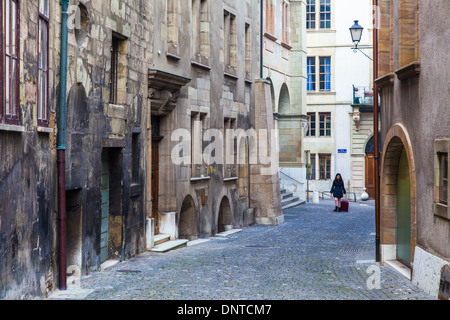 Young woman with suitcase in a street of Old Town, Gevea, Switzerland - Stock Photo