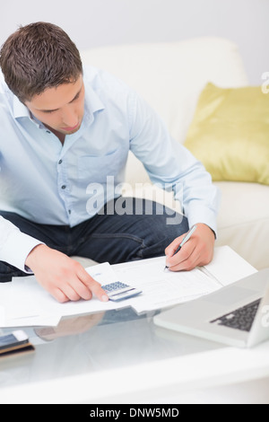 Young man with bills, calculator and laptop at home - Stock Photo