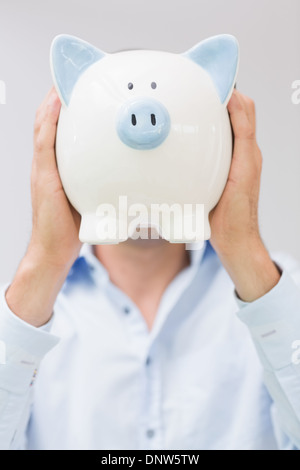 Casual man holding piggy bank in front of his face - Stock Photo
