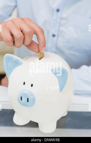Close-up mid section of a man putting coin into piggy bank - Stock Photo