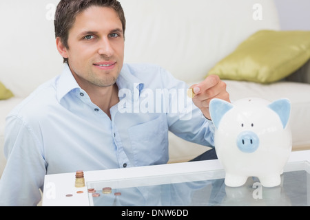 Casual man putting some coins into a piggy bank in living room - Stock Photo