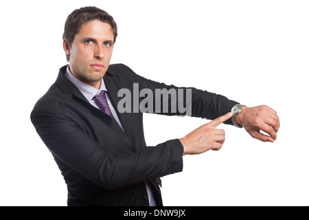 Portrait of a serious businessman showing his wristwatch - Stock Photo
