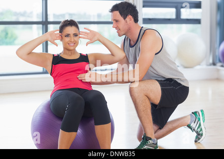 Trainer helping woman do abdominal crunches  on fitness ball - Stock Photo