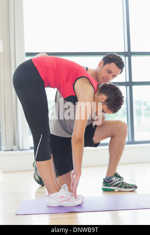 Male trainer assisting woman with stretching exercises in fitness studio - Stock Photo