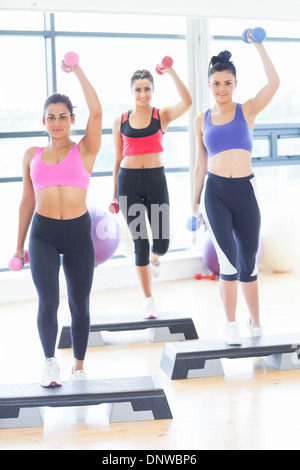 Fitness class performing step aerobics exercise with dumbbells - Stock Photo