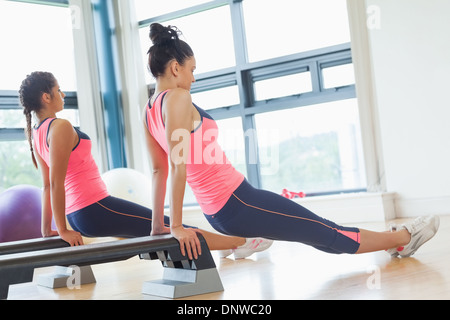 Two fit women performing step aerobics exercise in gym - Stock Photo