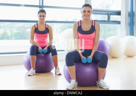 Two fit women with dumbbells on fitness balls in gym - Stock Photo