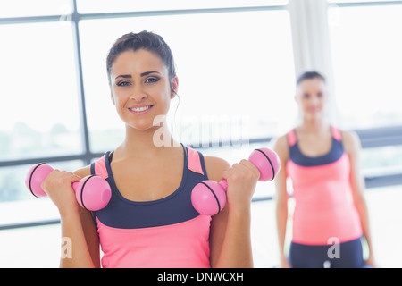 Fit woman lifting dumbbell weights with friend in background at gym - Stock Photo