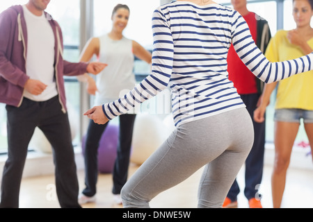 Mid section of fitness class and instructor doing pilates exercise - Stock Photo