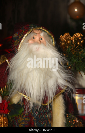 Decorative Santa Claus ornament under Christmas tree UK - Stock Photo