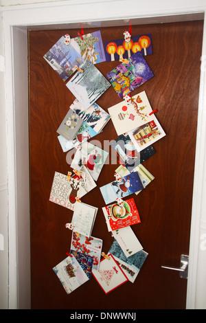 Christmas cards stuck on back of door - Stock Photo