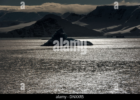 ANTARCTICA - An iceberg is silhouetted against the sun catching the water in the Gerlache Strait on the western - Stock Photo