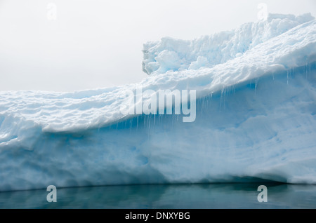 ANTARCTICA - Small icicles hang from a ledge of an iceberg. - Stock Photo