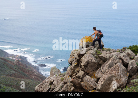 Female hiker overlooking Benijo village from coastal footpath in the Anaga mountains on Tenerife, Canary Islands, - Stock Photo
