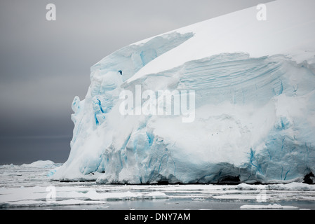 ANTARCTICA - A glacier of thick ice and snow gradually falls into the sea as it flows down the side of the mountains - Stock Photo