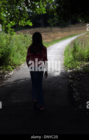 Young girl walking along a path. Back to camera. - Stock Photo