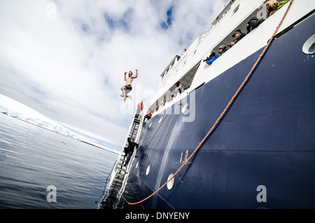 ANTARCTICA - Passengers take the polar plunge, diving into the freezing waters from the side of the ship near Melchior - Stock Photo