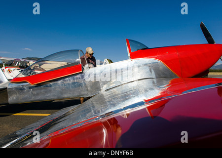 Visitor inspects a Van's Aircraft RV8; Antique and modern airplanes at the annual Salida ArtWalk Fly-In event - Stock Photo