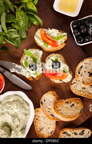 Crostini with mozzarella and fresh basil and olives - Stock Photo