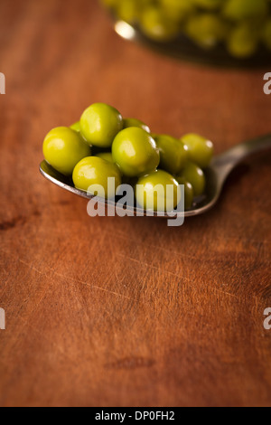 Open Glass jar of preserved peas on the dark background - Stock Photo