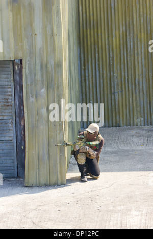 paintball extreme sport players in protective camouflage uniform and mask with markers gun in the field. - Stock Photo