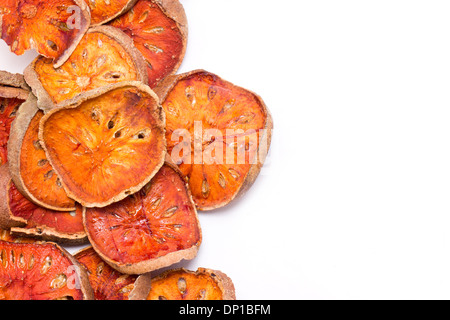 Slices of dried bael fruit isolated on white. - Stock Photo