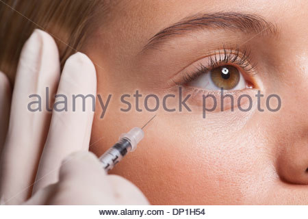 Close up of woman receiving botox injection under eye - Stock Photo