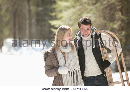 Smiling couple with sled walking in snowy woods - Stock Photo