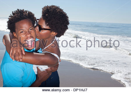 Smiling couple playing on beach - Stock Photo