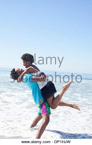 Man carrying woman on beach - Stock Photo