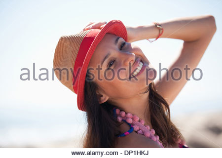 Smiling woman wearing sun hat on beach - Stock Photo