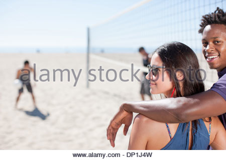 Couple standing on beach volleyball court - Stock Photo