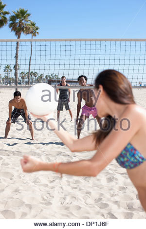 Woman playing beach volleyball with friends - Stock Photo