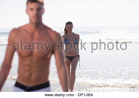 Couple playing in waves on beach - Stock Photo