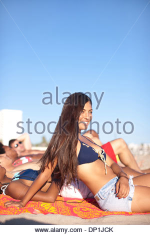Woman sitting with friends on beach - Stock Photo