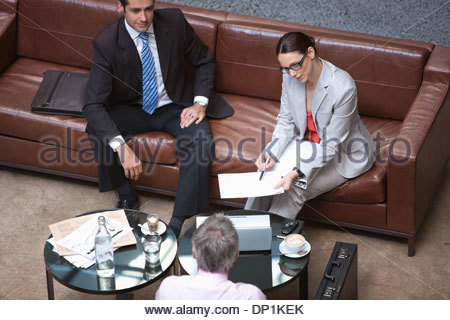 Business people meeting in lobby - Stock Photo