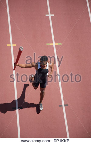 Runner running with torch on track - Stock Photo