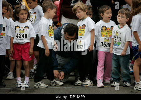 May 06, 2006; San Diego, CA, USA; ARTURO REYNOSO, center, ties the shoes of his son, ARTURO, 5, as his other son, - Stock Photo