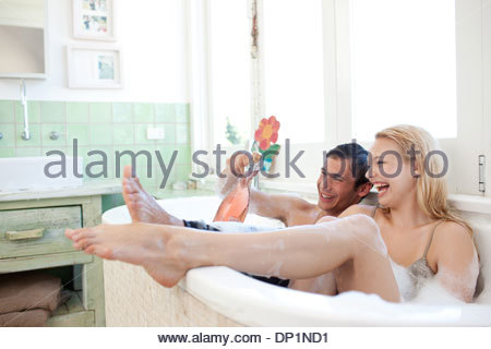 Couple in clothing drinking champagne in bathtub - Stock Photo
