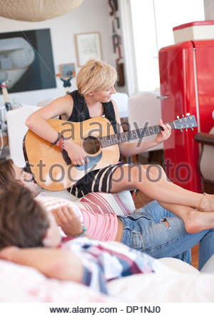 Woman with bare feet playing guitar for men on sofa - Stock Photo