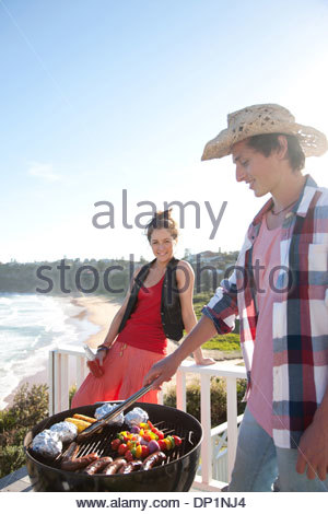 Man and woman tending barbecue with ocean in background - Stock Photo