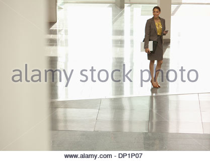 Business Woman standing and using cell phone - Stock Photo