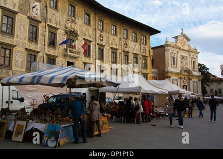 Market stalls in front of Palazzo dei Cavalieri the knights palace Piazza dei Cavalieri the Knights Square, old - Stock Photo