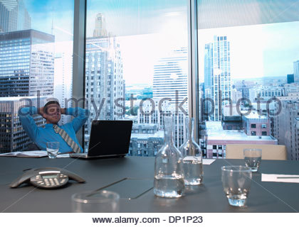 Smiling businessman with hands behind head in conference room - Stock Photo