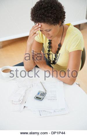 Smiling woman sitting at table paying bills - Stock Photo