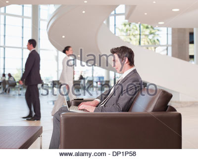 Businessman working in office waiting area - Stock Photo