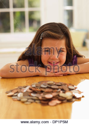 Smiling girl looking at pile of coins - Stock Photo